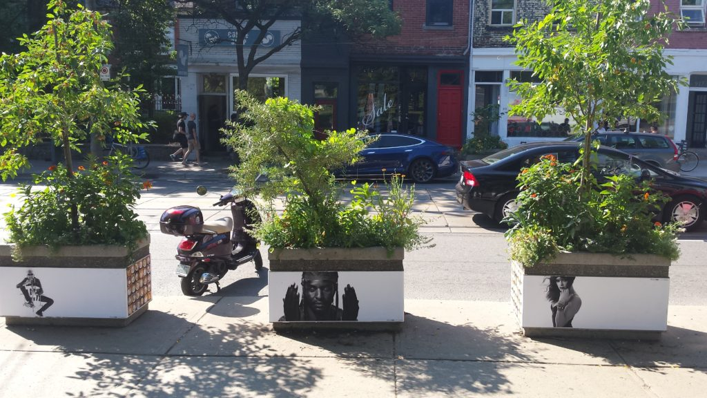 Planters line Queen Street West in front of Trinity Bellwoods Park